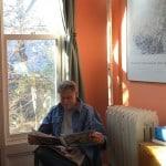 Dan reading in blue wicker chair in bedroom, amused that I am taking his photograph.