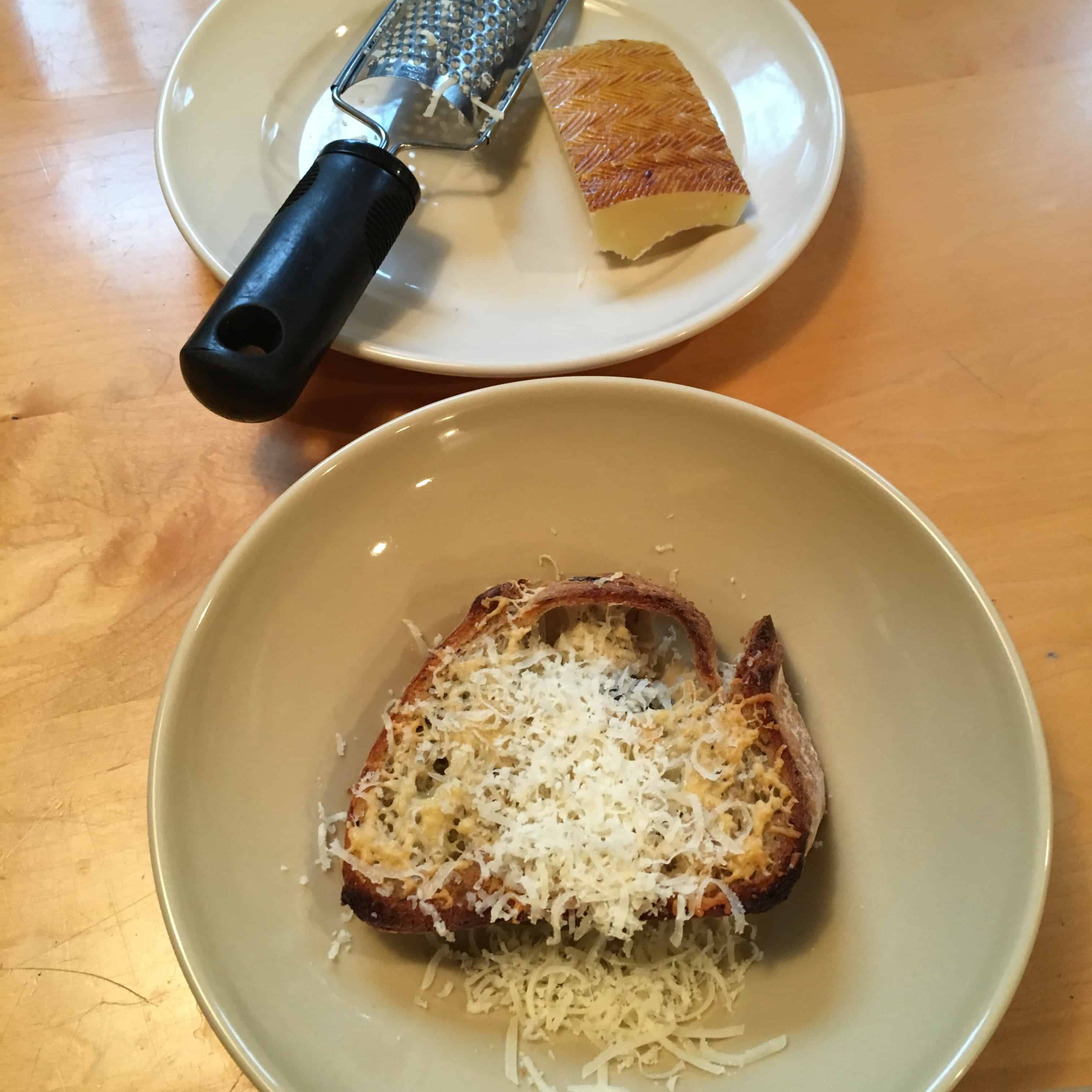 Preparing the garlic rubbed toasted bread with grated Parmesan cheese for the soup to come.