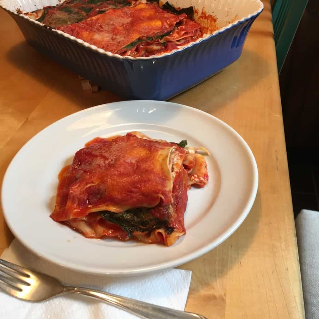 Serving a portion of lasagna with collard greens.