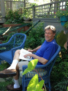 Dan reading in the garden with elephant ears plant in the foreground.