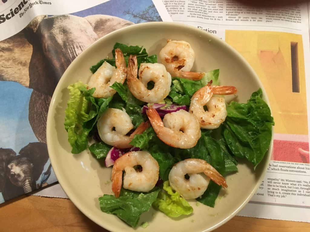 Sauteed shrimp over salad greens and red cabbage, with avocado dressing.