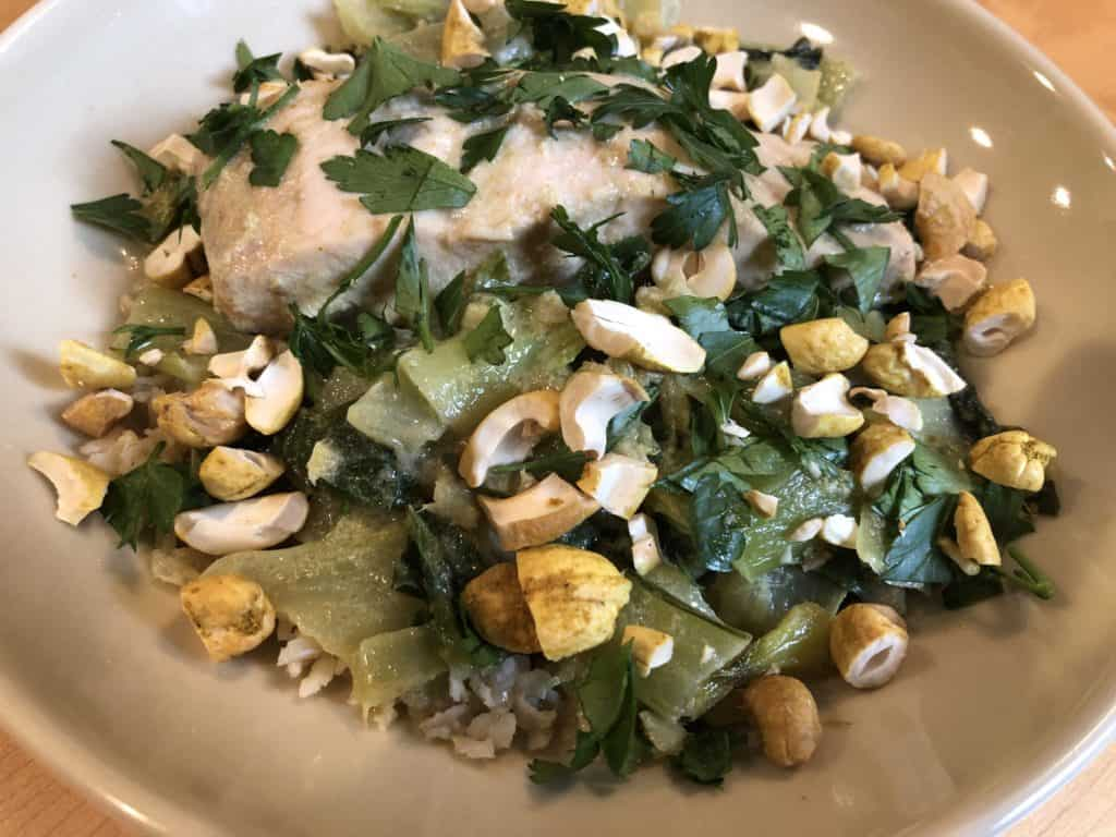 Salmon and Bok Choy Green Coconut Curry on a bed of basmati brown rice and garnished with cilantro and chopped cashews.